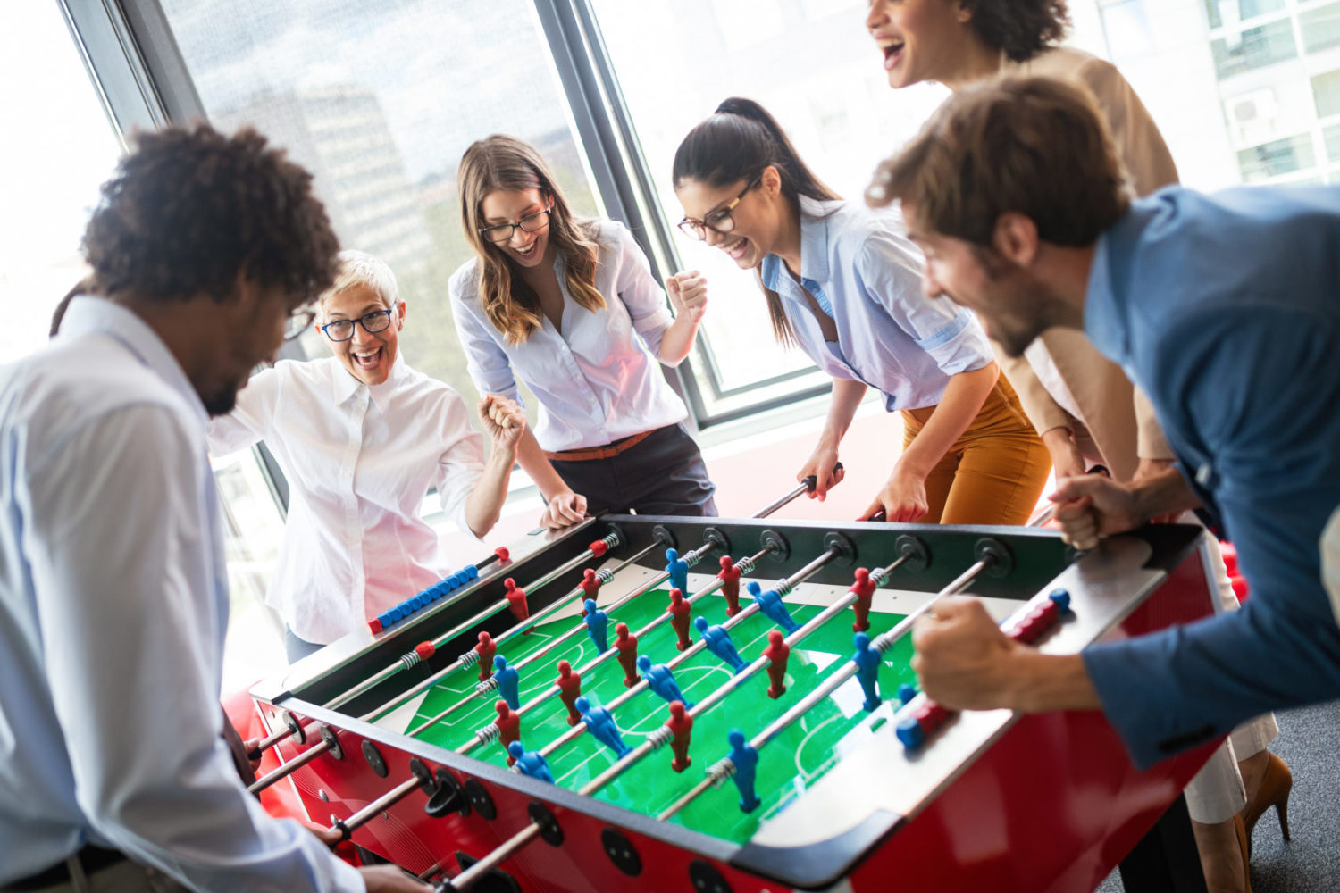 Coworkers gather around a foosball table for a fun game at Window Nation Headquarters