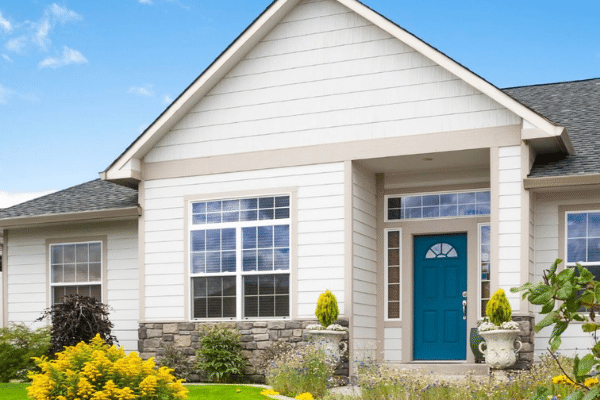 Home exterior with blue front door and large picture replacement window